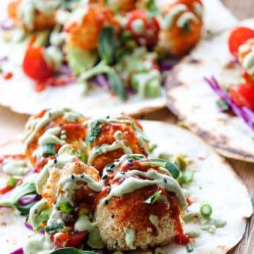 Sriracha cauliflower wings with thai sauce on taco shell.