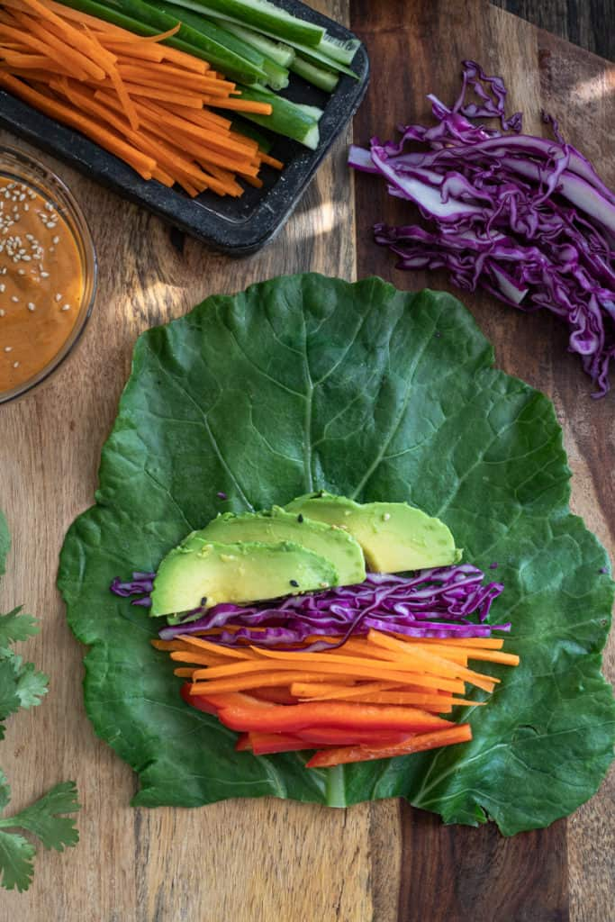 Collard green leaf with carrots peppers and avocado for a wrap.