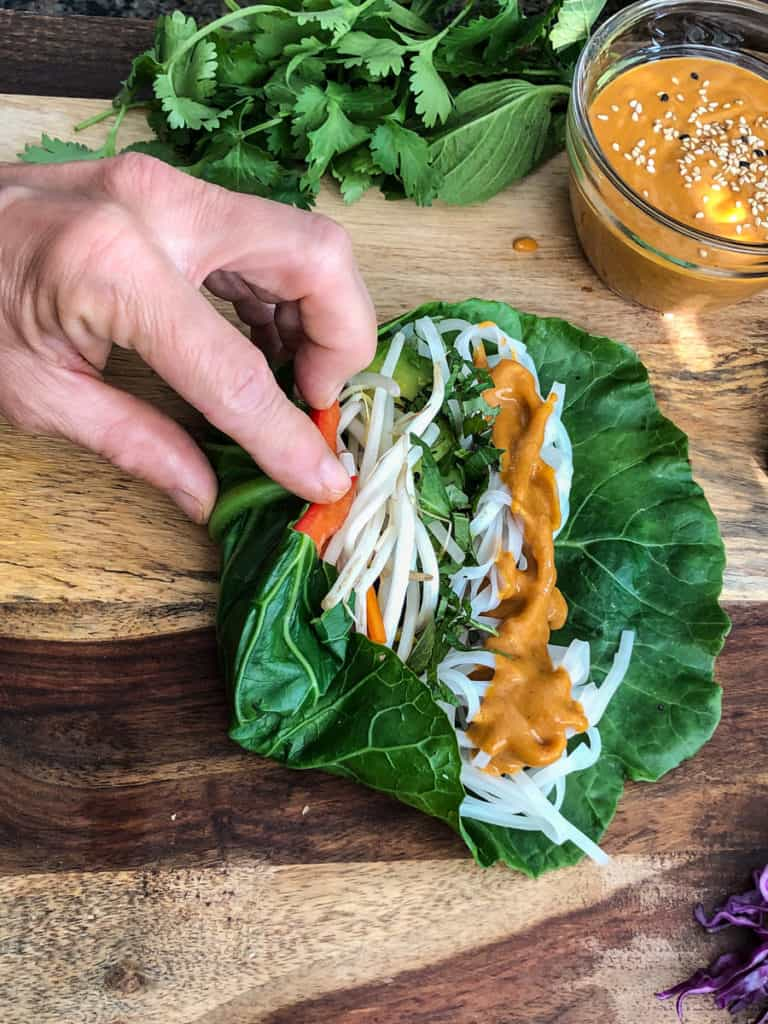 Large collard green leaf stuffed with vegetables and noodles being rolled.