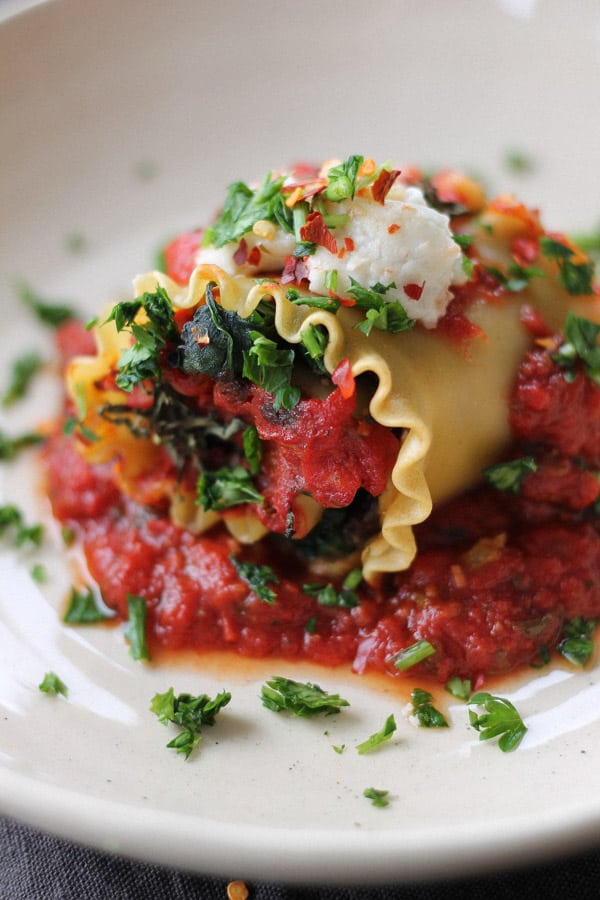 Vegan lasagna roll up sitting in a puddle of marinara sauce and topped with dairy-free cheese.