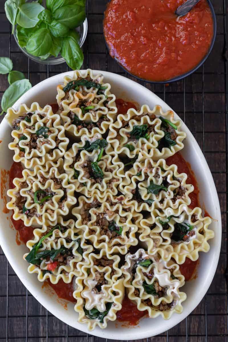 Vegan lasagna roll ups in baking dish.