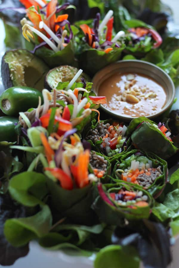 Plateful of raw summer lettuce wraps with noodles and spicy peanut sauce.