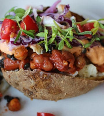 baked potato stuffed with vegetable, beans, and cashew cream on a plate