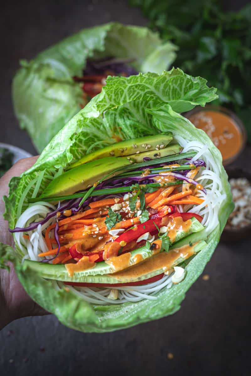 Vegetable and noodles in a lettuce cup with peanut dipping sauce.