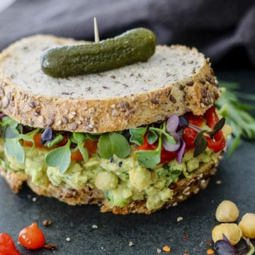 chickpea sandwich on sourdough with leafy greens and hot peppers