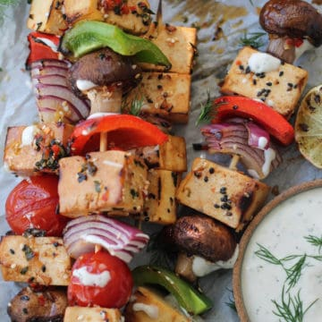 Skewers of tofu and vegetables with a bowl of dipping sauce.