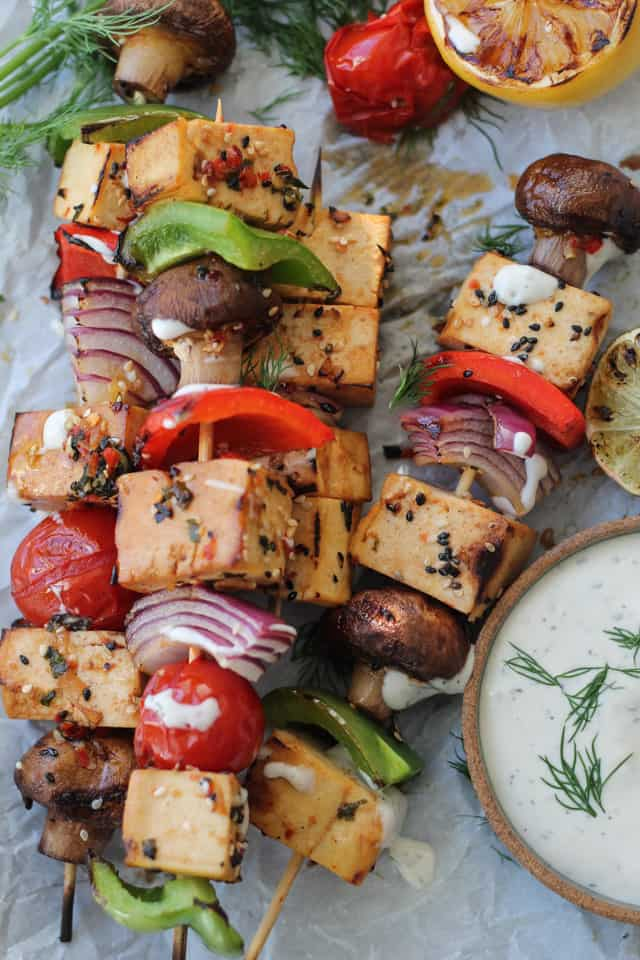 Skewers of spicy tofu, tomatoes and mushrooms on a tray with a bowl of dilly dipping sauce.