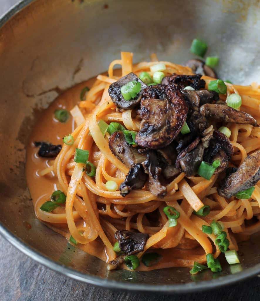 Spicy Dan Dan Noodles in a pan topped with mushrooms and scallions.