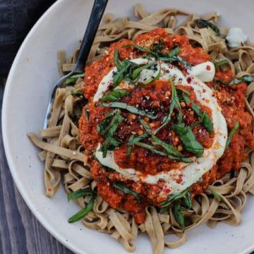 Bowlful of Vegan Eggplant marinara sauce on pasta with a drizzle of cashew cream.