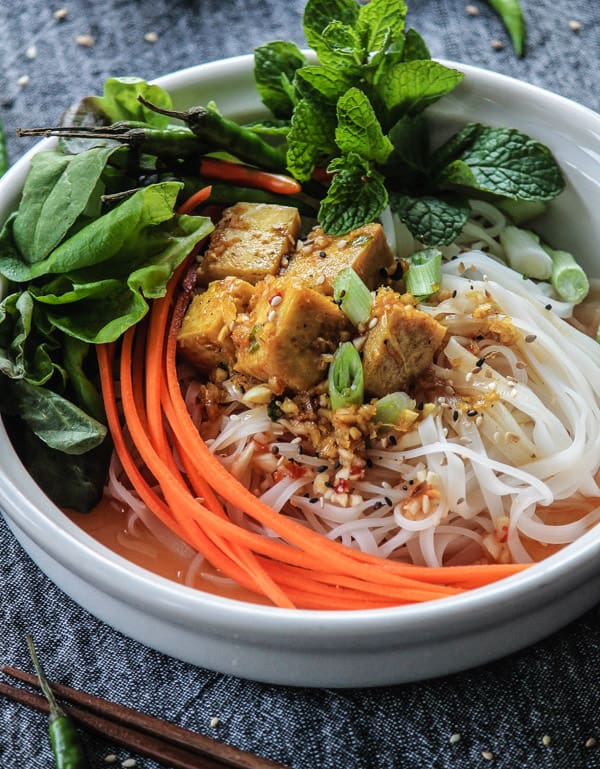 Grill Tofu noodle bowl with lemongrass marinade, julienne carrots and fresh mint and basil leaves.