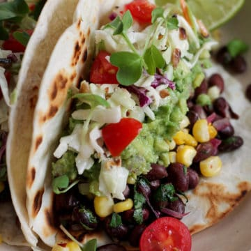 Vegan Corn and black bean tacos with slaw and tomatoes.