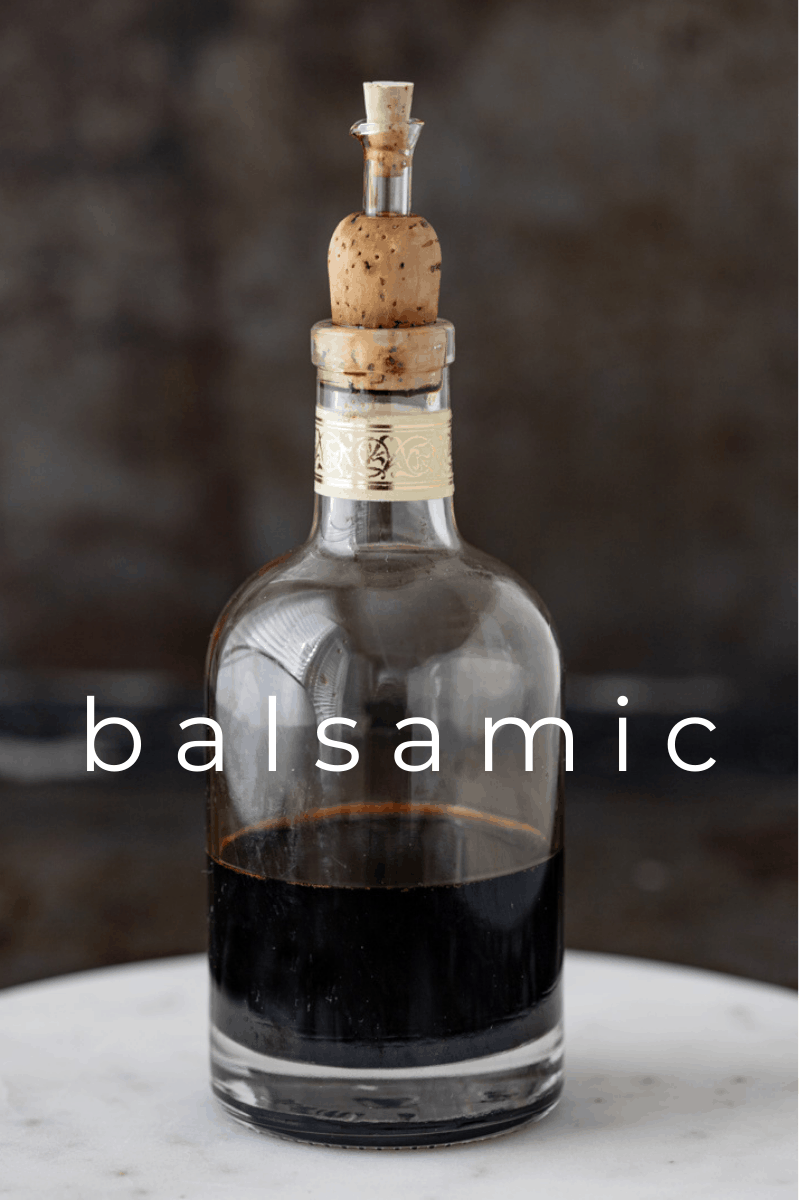 Bottle of balsamic reduction sitting on white marble dish.