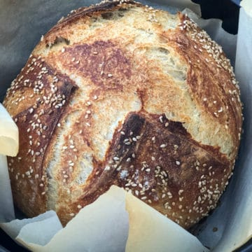 Freshly baked rustic bread surrounded by baking paper in a Dutch oven.