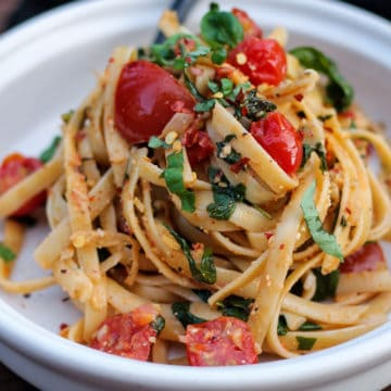 Large tangle of fettuccine with tomatoes and spinach on a plate.