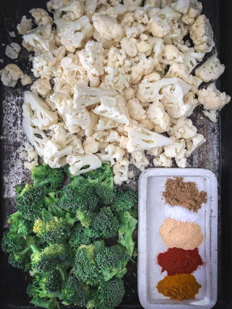 Chopped cauliflower and broccoli on a baking sheet with spices for soup.