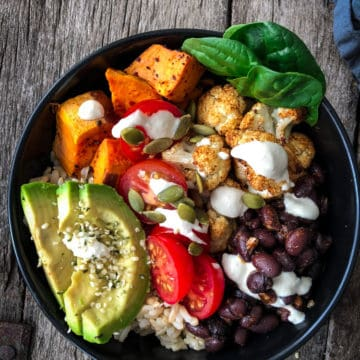 Vegan taco bowl with rice, beans, sweet potatoes, avocado and sauce drizzles.