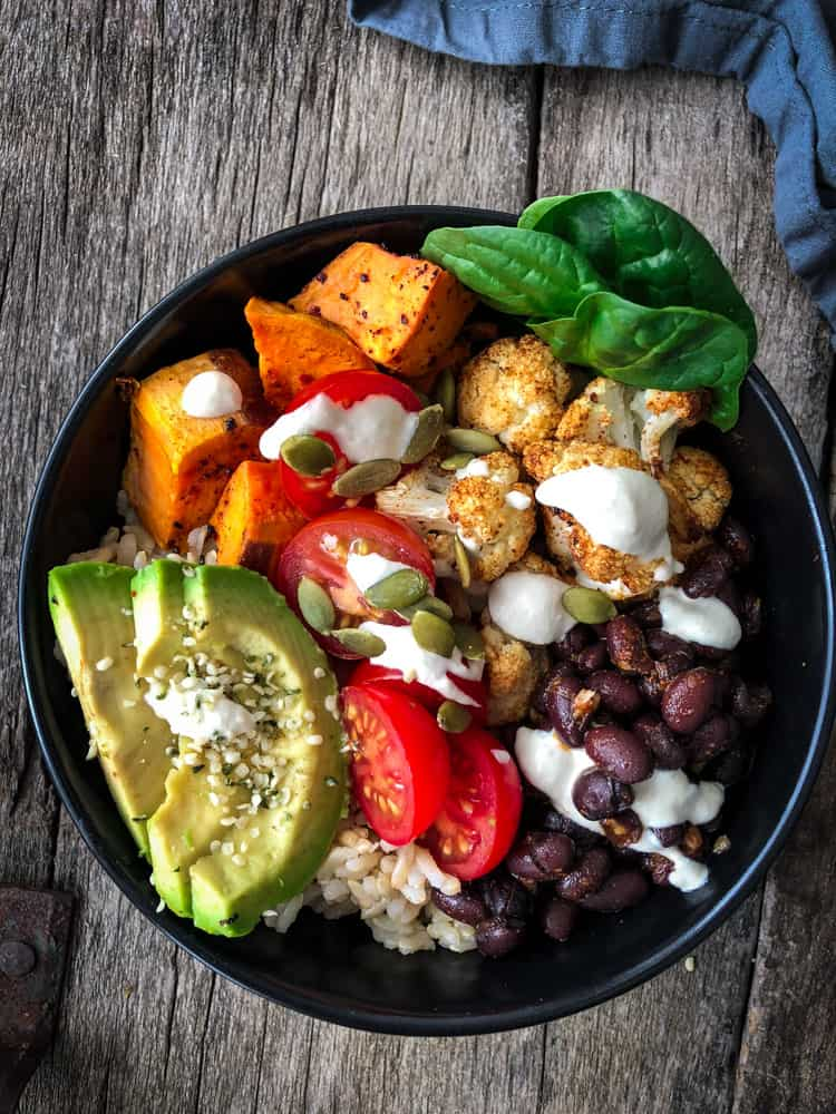 Veggie rice bowl with spicy baked cauliflower, sweet potatoes, tomatoes, avocado pieces, black beans and saucy drizzle.