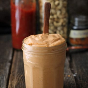 Thick cashew cream in a jar with spoon sticking up