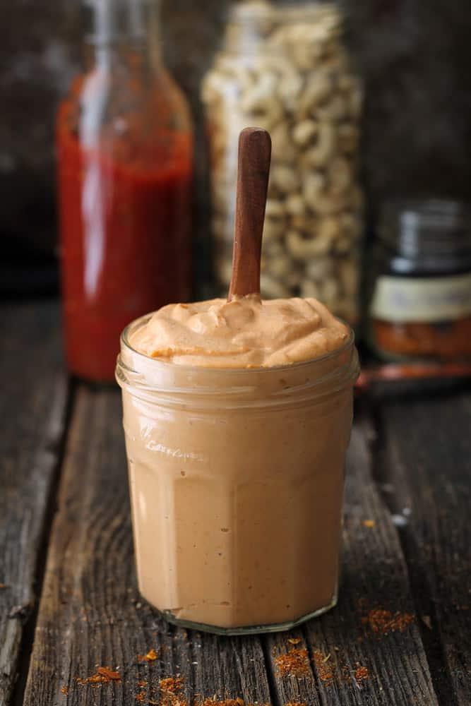 A jar of creamy tex-mex cashew sauce sitting on a cutting board/