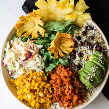 Jackfruit Buddha bowl with rice, avocado, beans, slaw and corn in a bowl.
