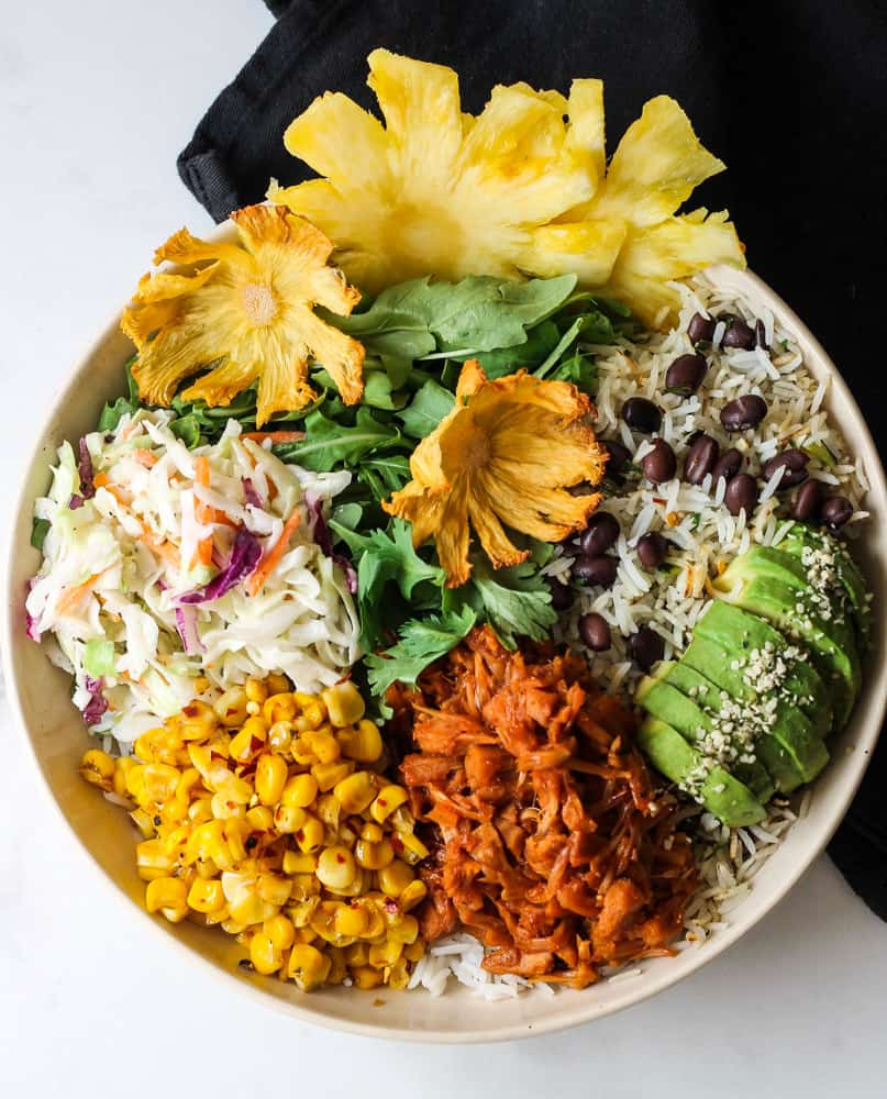 Sweet and spicy jackfruit leftover bowl with pineapple flower, rice and beans, slaw and avocado.