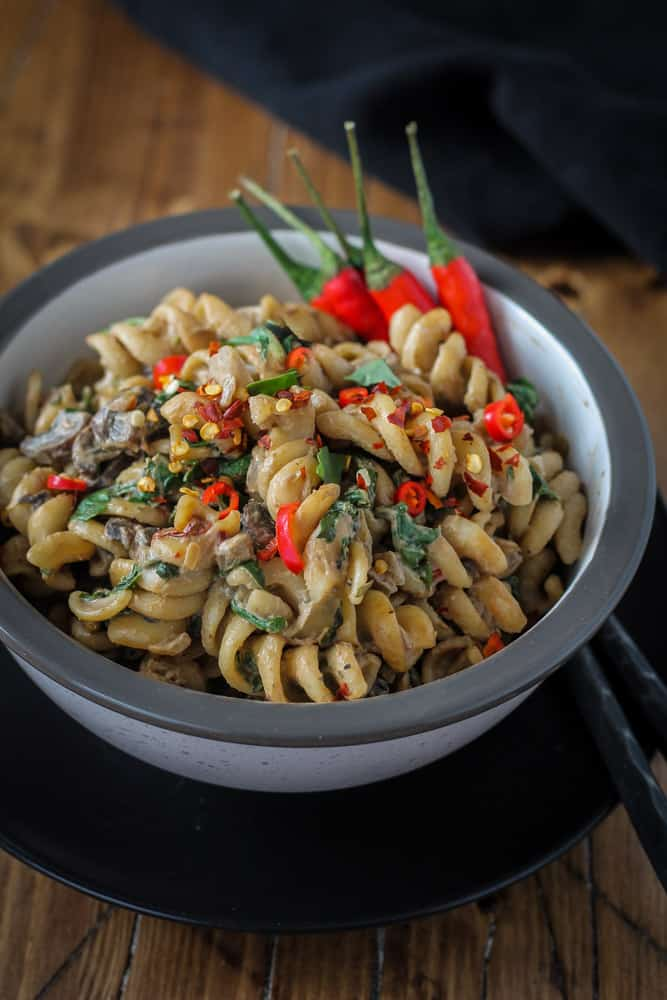 Bowl of mushroom pasta with red hot peppers on top.