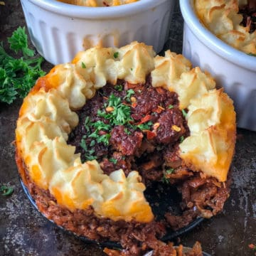 Vegan Shepherd's pie filling piped with mashed potatoes baked in individual mini pots.
