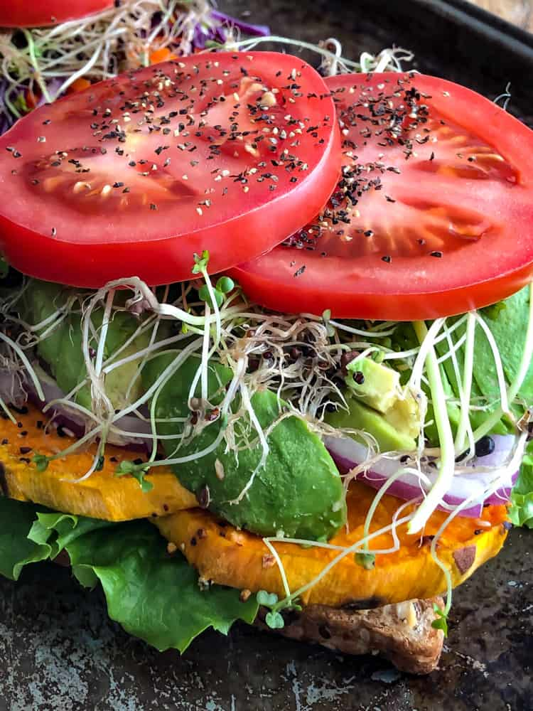 Open faced vegetable sandwich with sweet potato, tomato, avocado, and sprouts.