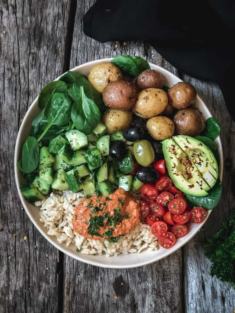 Vegan Buddha bowl made with Greek potatoes, avocado, olives, and harissa red pepper sauce.