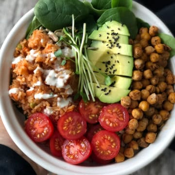 Mexican rice and chorizo chickpea bowl with tomatoes and half an avocado in a bowl.