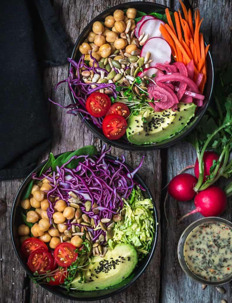 Two salad bowls, lemon dressing and fresh radishes on counter.