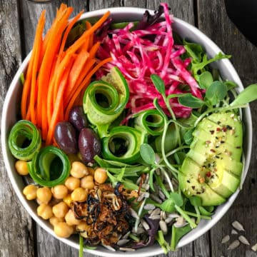 Bowl of green salad with carrots, avocados and beans.