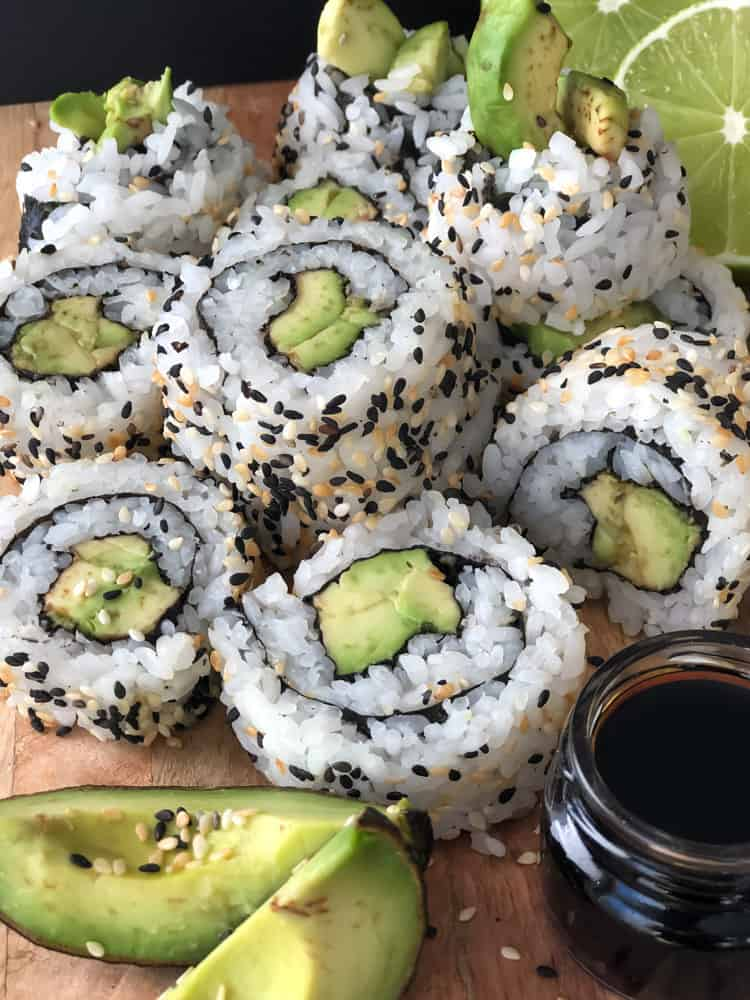 Vegan sushi made with avocado piled on a serving plate with a dish of soy sauce.