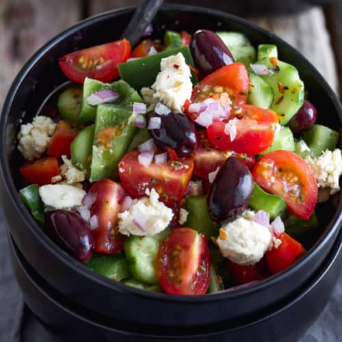 Vegan salad with feta tomatoes olives and greek salad dressing in a bowl