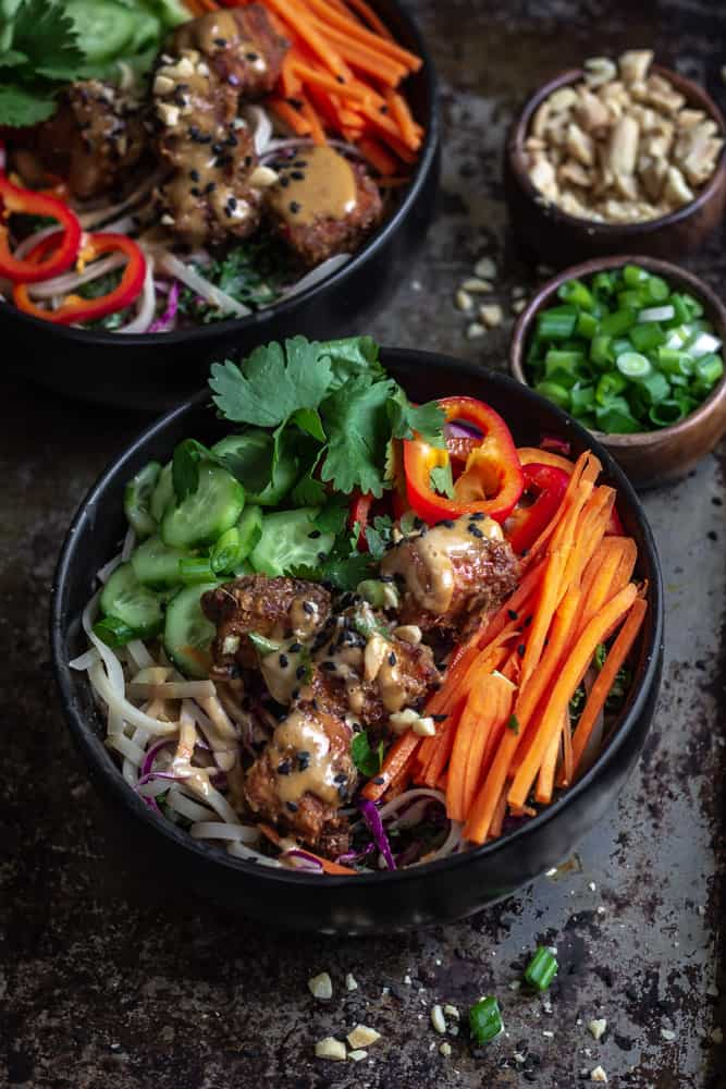 Spicy peanut tofu bowls with fresh vegetables on rice noodles sitting on a baking sheet.