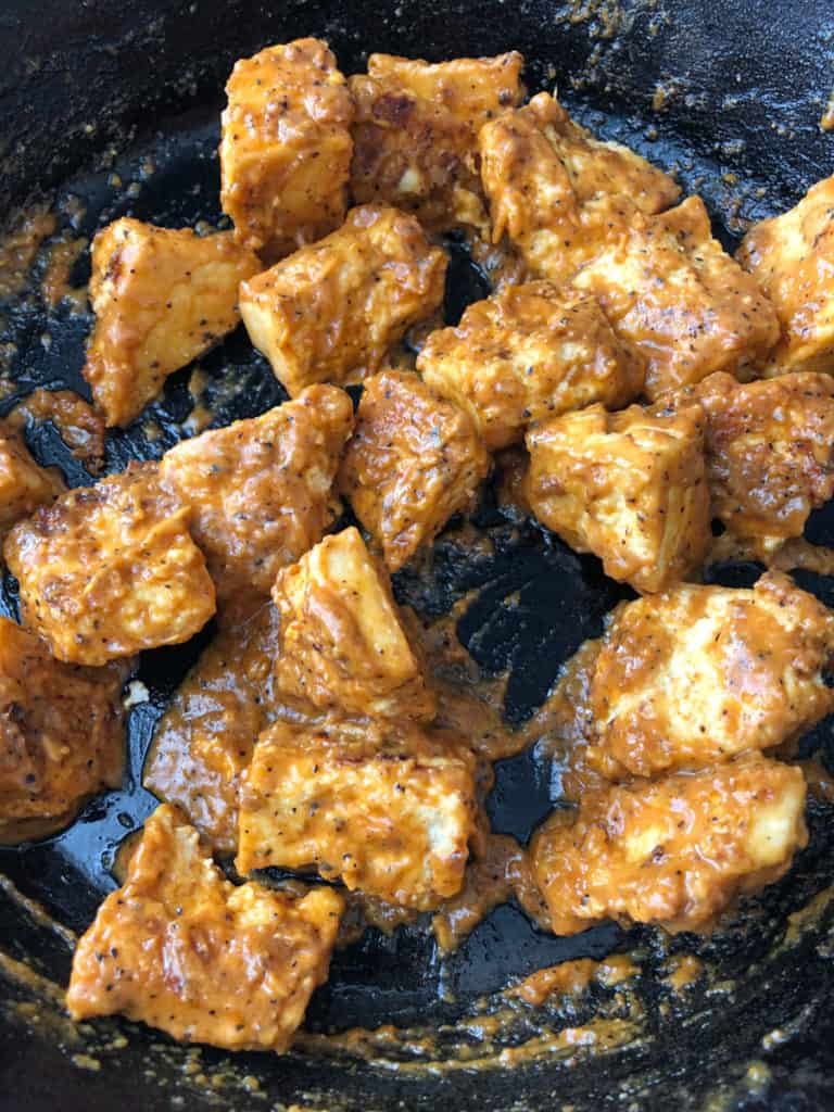 A skillet full of tofu in spicy peanut satay sauce.