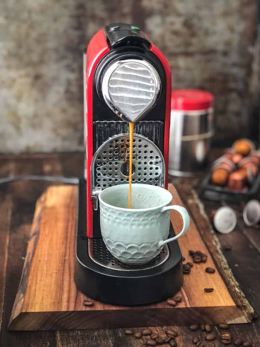 Automatic coffee maker with cup inserted making an espresso shot at home.