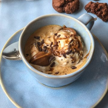 Coffee and ice cream with a caramel drizzle and chocolate sprinkles served in blue cup.
