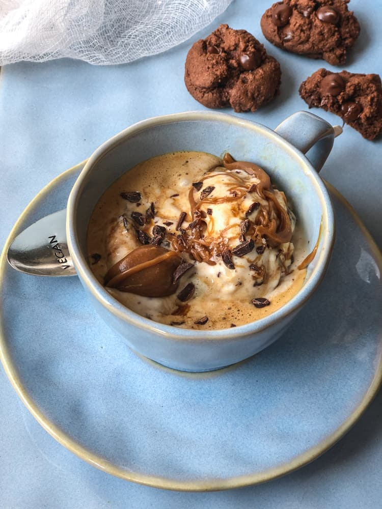 A coffee cup filled with ice cream, caramel and chocolate.