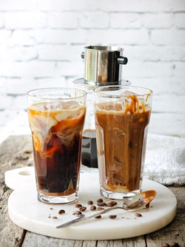 Two tall glasses of dairy-free iced coffee with a drip of vegan caramel sauce.