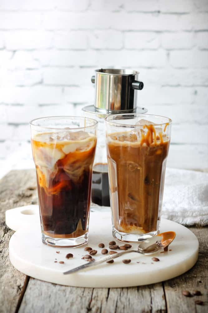 Two tall glasses of iced coffee with caramel sauce.