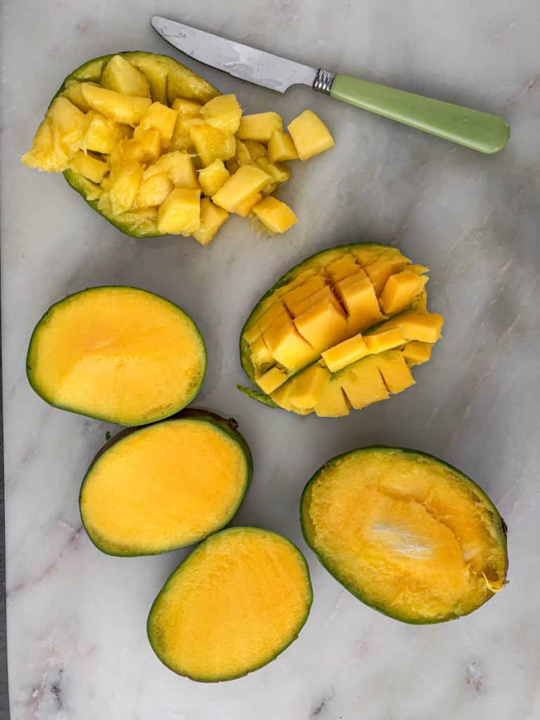 Sliced and chopped mangos on a cutting board with a knife.