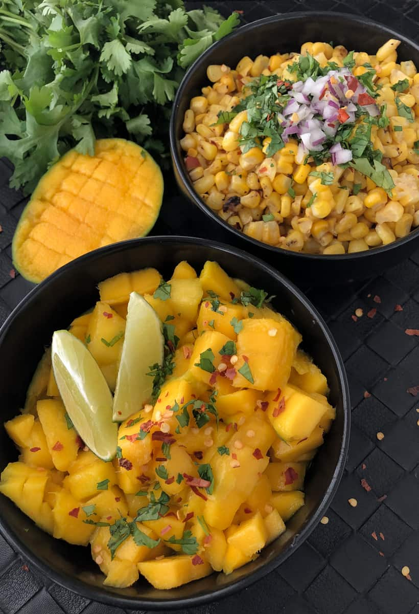 Bowls full of chopped mango and grilled corn on a cutting board.