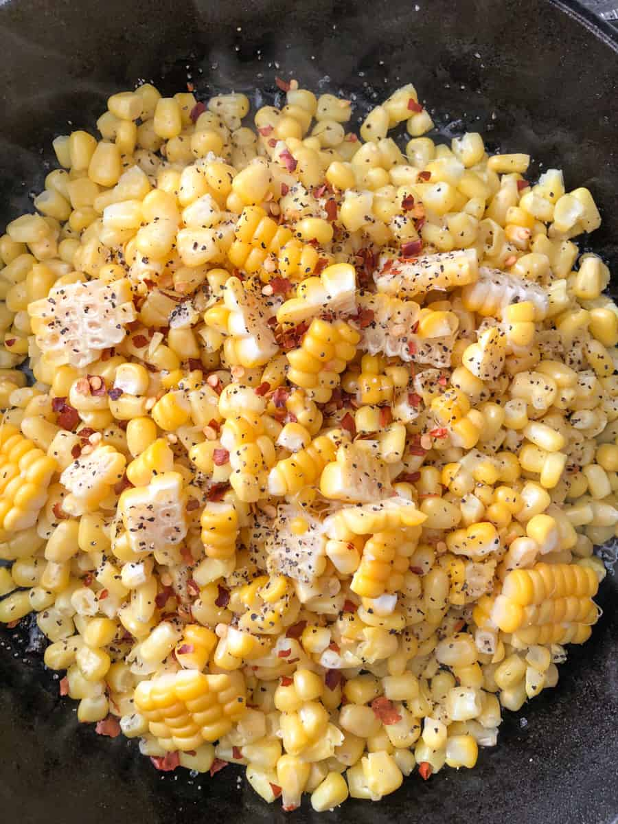 Large pan of grilled corn niblets topped with spices.
