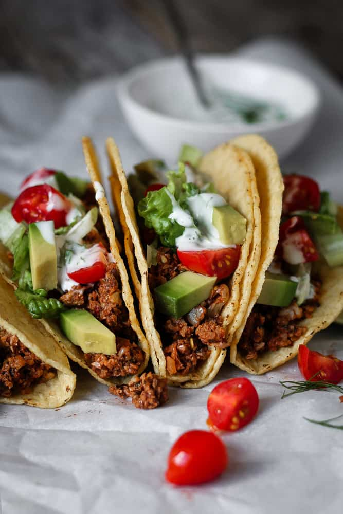 Spicy vegan tofu meat tacos topped with tomatoes avocado and tangy sauce.