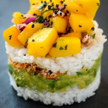 Avocado, sweet potato and mango salsa layers stacked on rice.