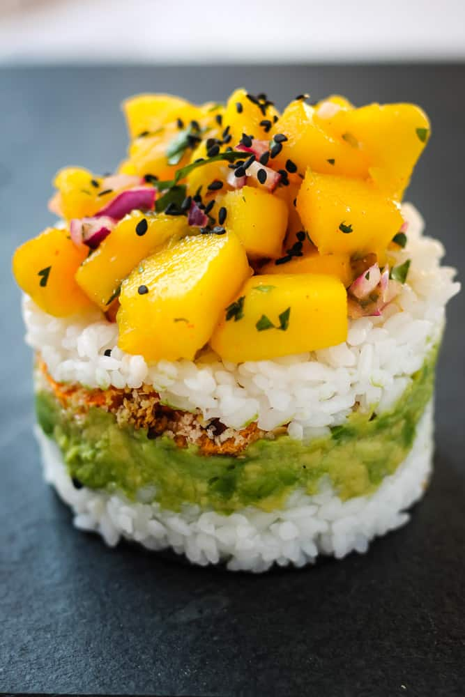 Avocado slices and Mango salsa stacked on a bed of sushi rice.