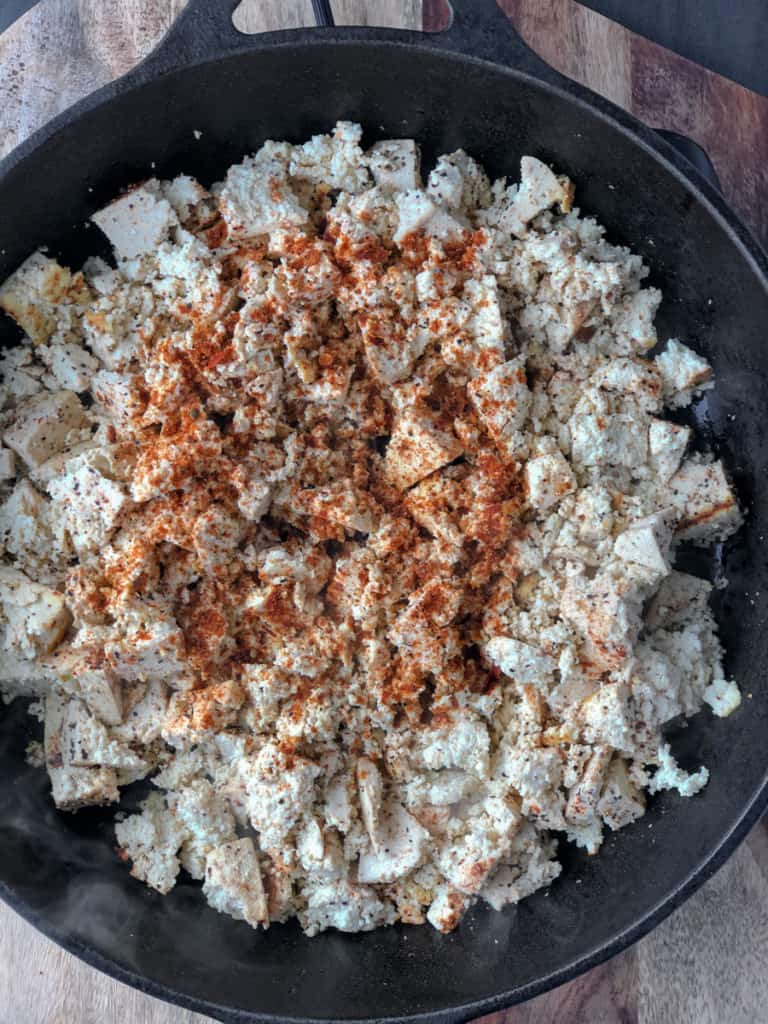 Frying pan with crumbled tofu and spices on top.