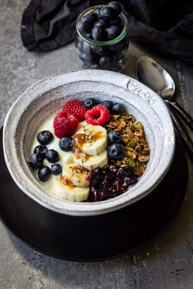 Bowl filled with plant based yogurt, homemade granola and juicy berries.