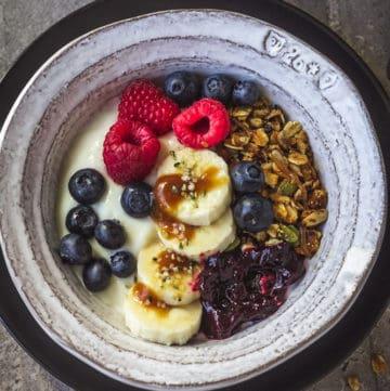 Crunchy granola, plant-based yogurt, and fresh berries in a bowl.